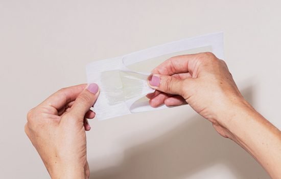women holding waxing strip without post-inflammatory hyperpigmentation