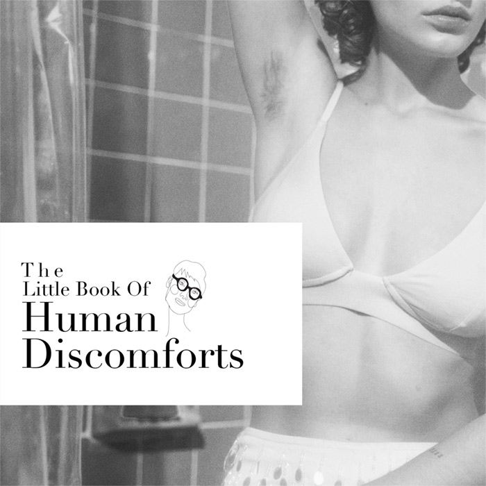 black and white image of woman wearing underwear in washroom exposing armpit with hair