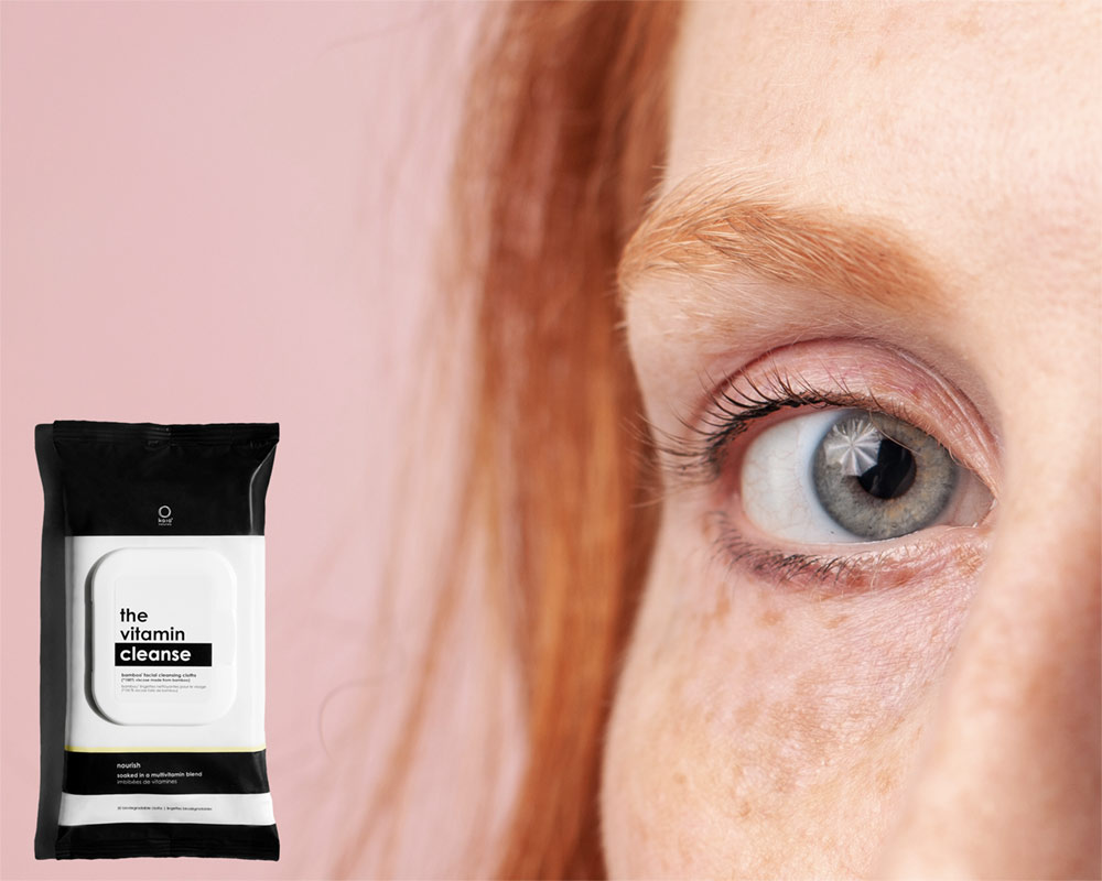 redhead woman's eye with freckles on pink background